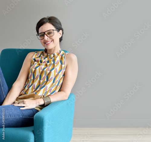 Smiling Trendy Girl Sitting In Blue Armchair Isolated