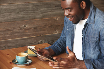 Rapturous African American man sitting in a caf?, enthusiastic about news or received messages from social networks. The guy is totally happy that forgot about his coffee and sweet pie lying on table.