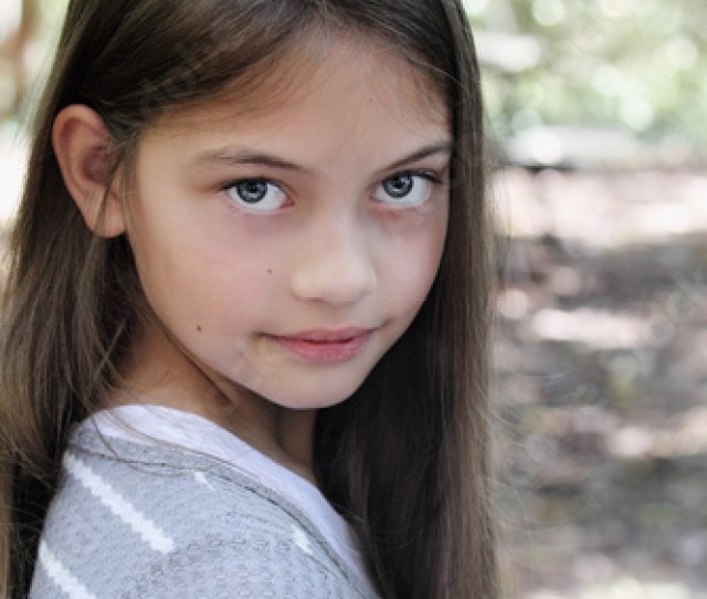 Young Pre Teen Kid With Long Hair Looking Directly Into The Camera