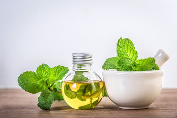peppermint essential oil in the bottle on the table with fresh green mint leaf