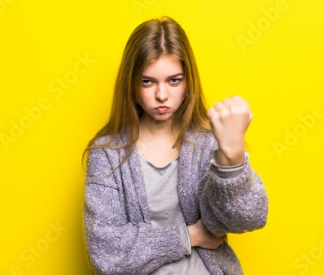 Beautiful Sad Young Teen Girl Close Up Threatens Fist Into Camera Isolated On Yellow Background