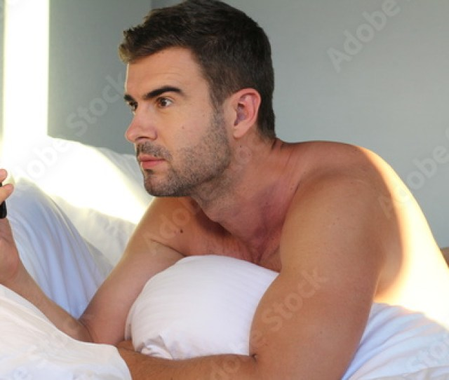 Handsome Naked Man Using Phone In Bed