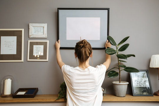 Girl hanging a frame on a gray wall Stock Photo   Adobe Stock