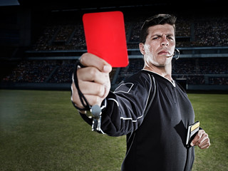 Referee flashing red card on soccer field