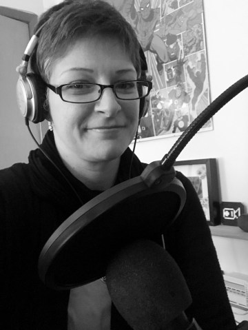 Image of the author wearing headphones and sitting in front of a microphone