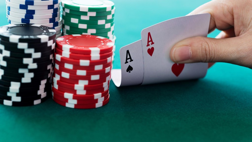 Photo of a person lifting poker cards next to a pile of poker chips