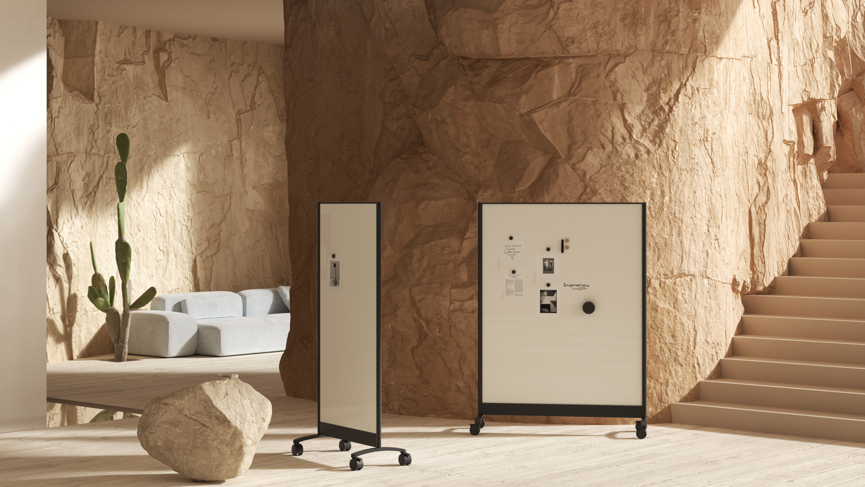 Two mobile dry erase boards in front of wall made of rock