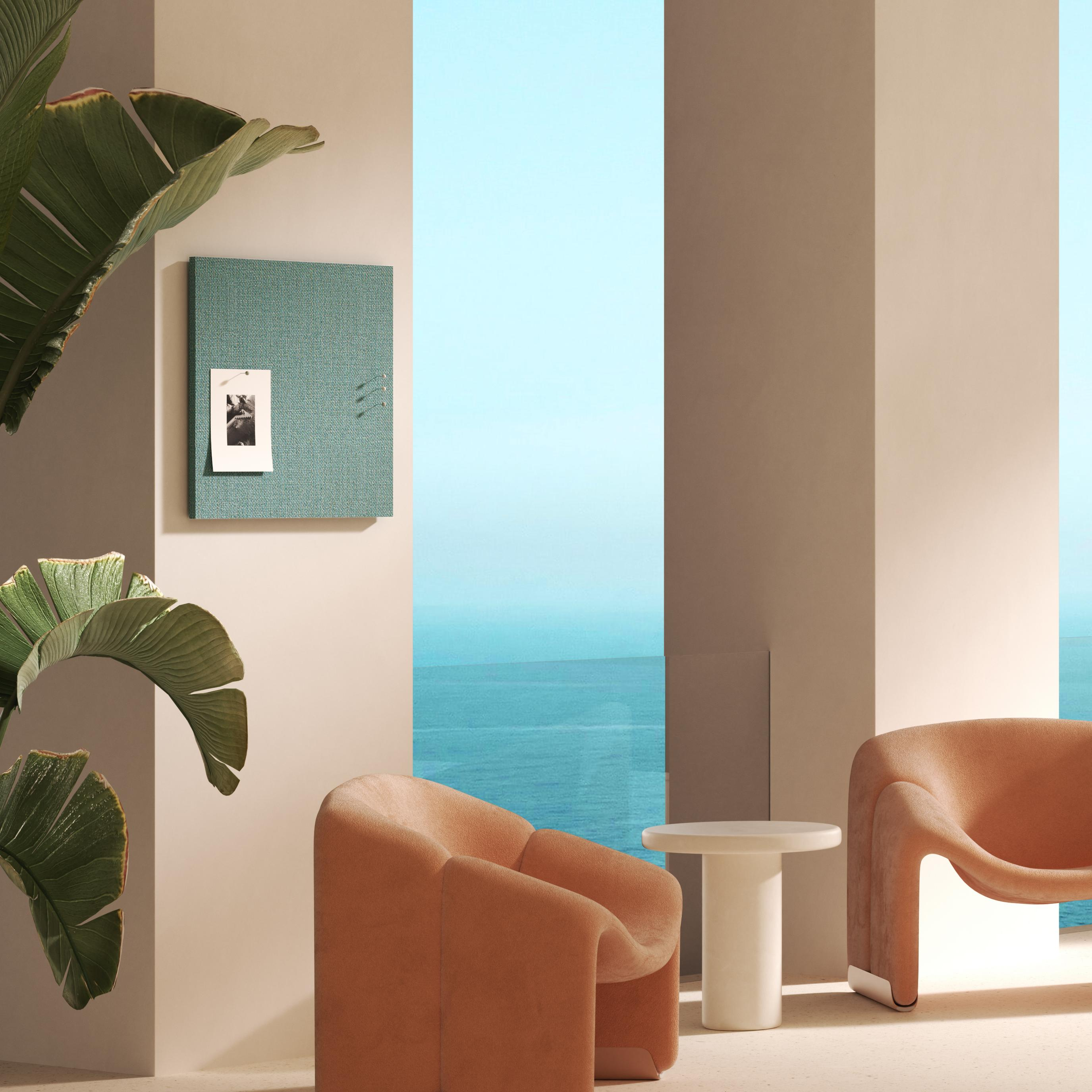 Dark turquoise tack board on wall with burnt orange chairs in room overlooking water