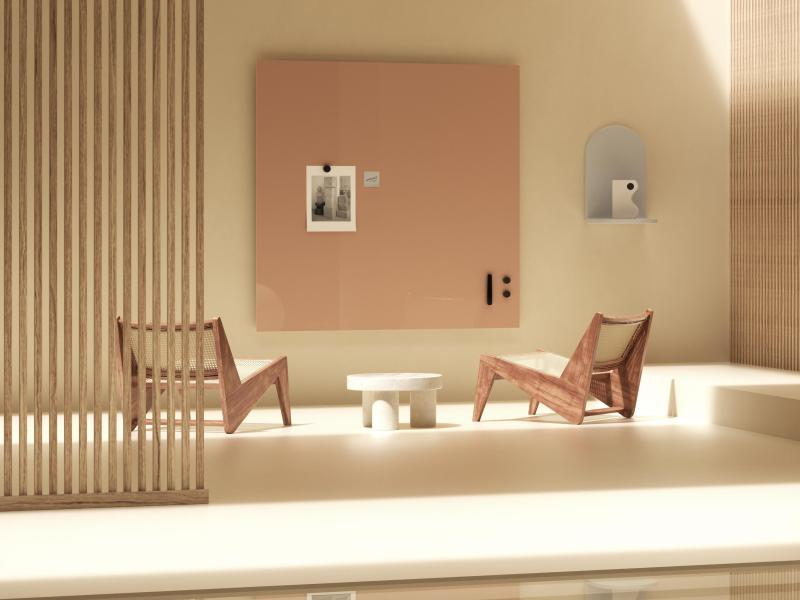 Blush colored whiteboard in meeting space with two lounge chairs
