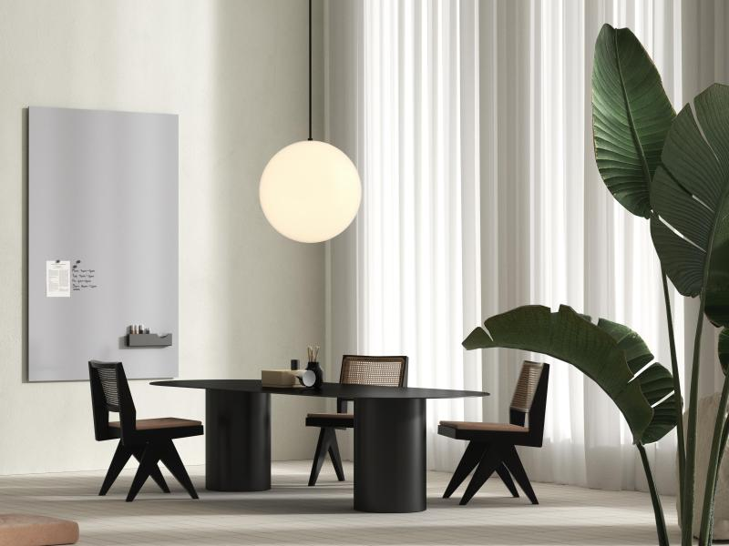 Modern workspace with dark conference furniture and vertical whiteboard on wall