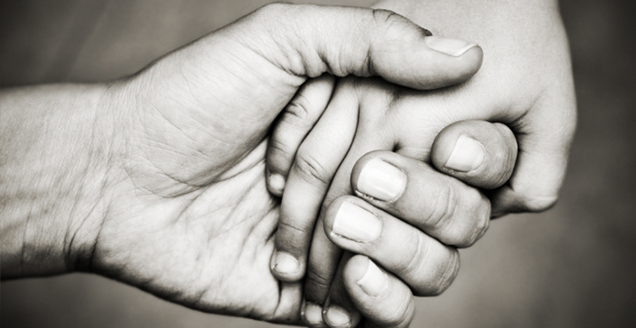 Photo of an adult hand holding a child's hand