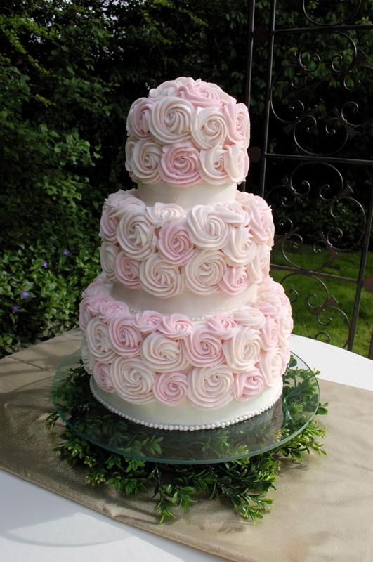 wedding cake with pink swirled icing roses