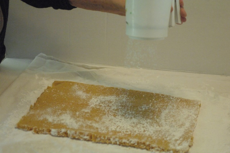 Flip the cloth up and over to distribute the excess Powdered sugar onto the other side of the cake.  Add more powdered sugar.