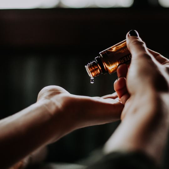 A woman pours massage oil into her hands