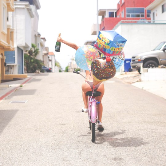 A woman on a bicycle in a bikini with champagne and birthday balloons