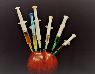 Syringes in a red apple on a black background