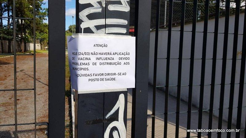 Cartaz fixado em frente a posto de vacinação