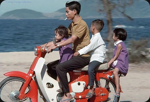 Người đàn ông và ba em bé trên chiếc Honda Dame C50 màu đỏ.