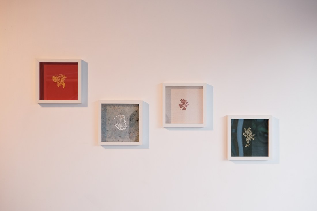 Four white frames are hung on a white wall, cascading downwards from the left. Far left, within the frame sits a yellow papercut over a red background. Centre left, is a blue speckled background with a white papercut. Centre right is a red papercut over a white background. Far right, there is a gold papercut over a green background.