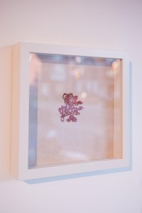 A photo of a small intricate red papercut of fluttering leaves sits in the centre of a white background. It is framed in a square white frame, hung on a blank wall. The photo is taken a little angled from the left side of the frame.