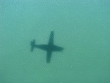 image of a Maya airplane shadow on the caribbean sea