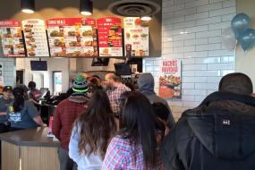 A line of customers waits inside a Taco John's.