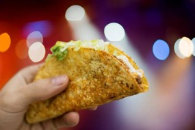 A hand holds a crispy hard-shelled taco in the foreground, with blurred lights glowing in the background.