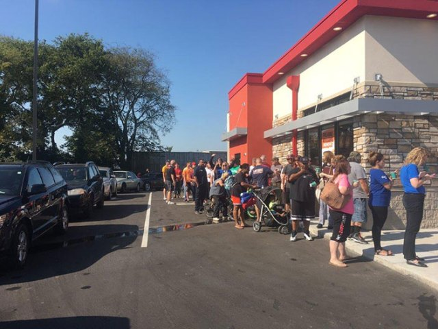 A long line of people stretch from the door of a Taco John's down a sidewalk and into the parking lot.
