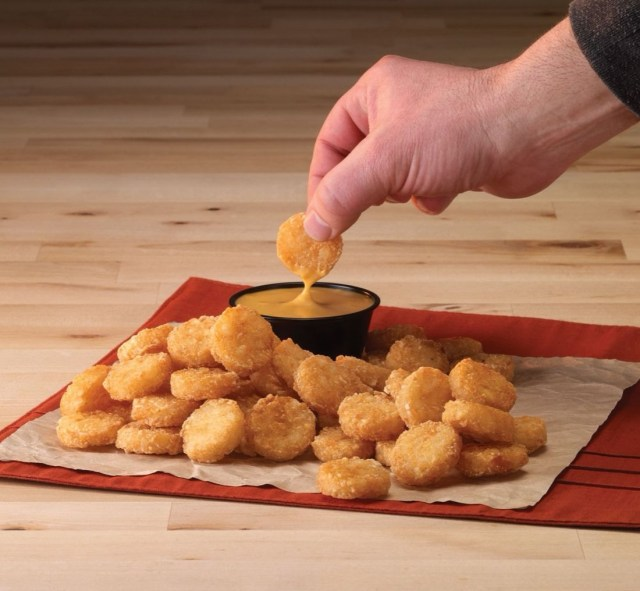 A hand is seen dipping a fried potato disk into a small black ramekin of melted cheese. A pile of the fried potato rounds surround the cheese dip on a napkin on top of a rust-colored placemat on a wooden surface.