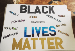 "A sign reads ""black lives matter"" with smaller text reading ""womxn, kids, teachers, grannies, sisters, parents, scientists, nerds, artists, friends."""