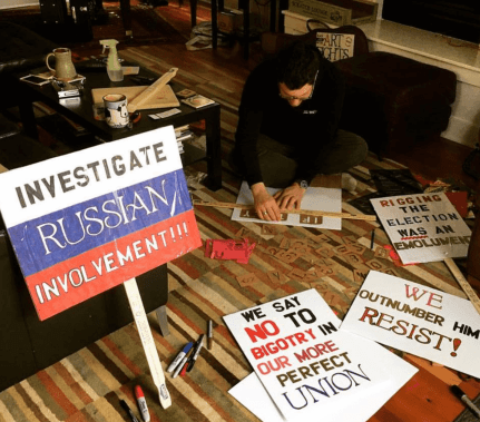 "A devastatingly handsome man hand stencils a protest sign. In the foreground are signs reading ""Investigate Russian Involvement!"" ""We say NO to bigotry in our more perfect union."" ""We Outnumber Him! Resist!"" and ""Rigging the election was an emolument."""