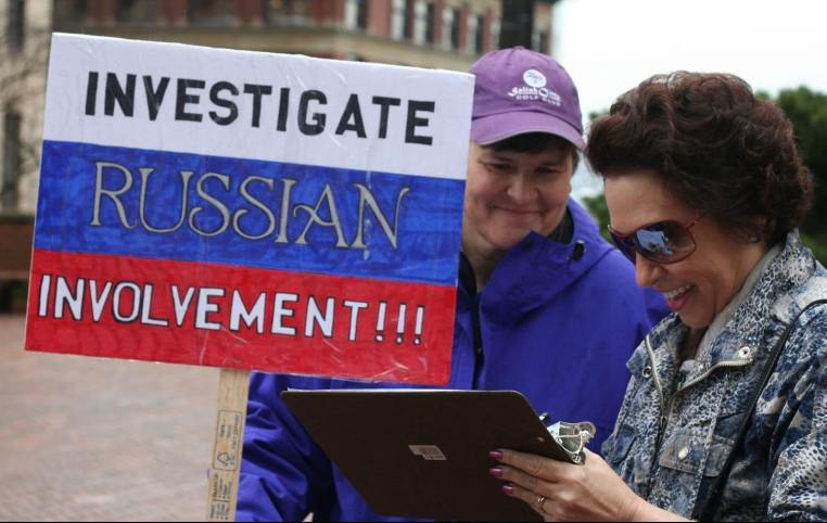 """A sign drawn on top of the Russian flag reads """"Investigate Russian Involvement!"""""""