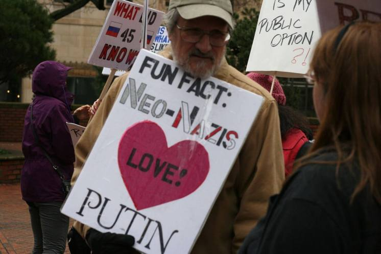"""A person holds a sign that reads, """"fun fact: Neo-Nazis love Putin."""""""