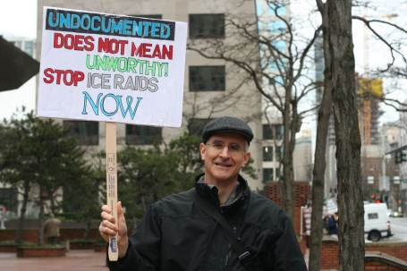 """A person holds a sign that reads, """"Undocumented does not mean unworthy. Stop ICE raids now!"""""""