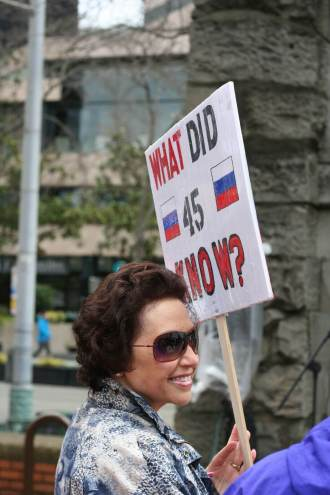 """A person holds a sign that reads, """"what did 45 know?"""" with Russian flags on either side of the number 45."""