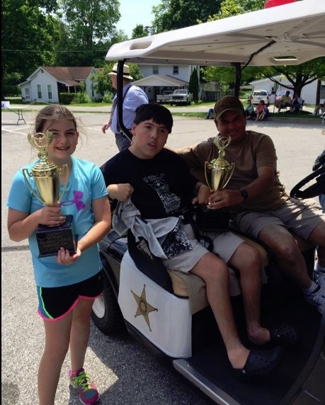 WHEEL WINNERS--The team of Carlie Gossett as the runner, Collin Watkins (center) riding shotgun, and Ray Watkins behind the wheel won the obstacle course of the Mayberry Squad Car Nationals during Mayberry in the Midwest. Photo by Stephanie Gossett.