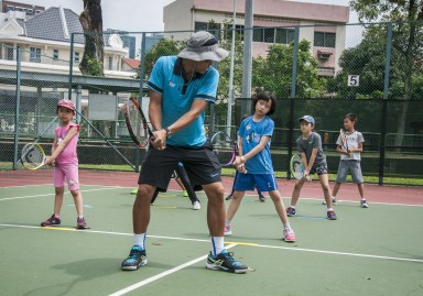 Junior Tennis Camp with coach showing child how to swing a racquet by TAG International Tennis Academy