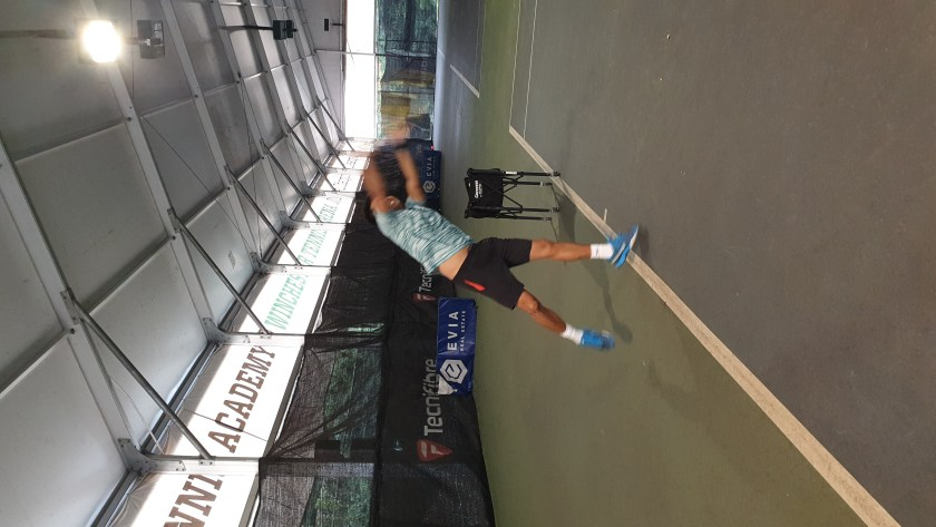 TAG International Tennis Academy's Coach Michael Mantua demonstrates a perfect platform Tennis Serve - note the deep leg bend, hip out, outer lat on stretch, and the shoulder over shoulder in the trophy position.
