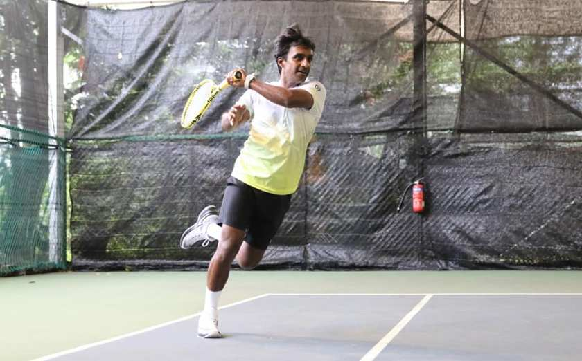 TAG Coach Parekh Pratim. Left handed players are less common, and their usual court position of their forehands make them difficult to play against. As seen in this photo, Coach Pratim hits an inside out forehand from the deuce court alley.