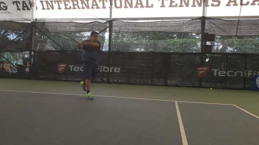 Coach Ten Rapeepat has a long follow through on his forehand