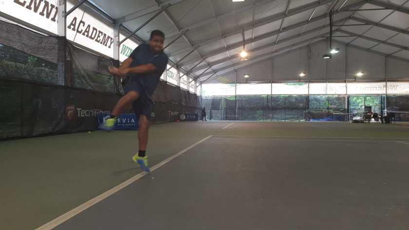 TAG Coach Rapeepat Thonghatta prepares to hit a high backhand
