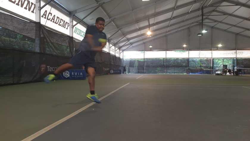 TAG Coach Rapeepat Thonghatta hits a high backhand