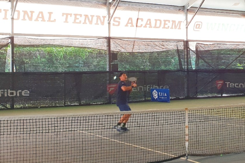 Coach Bo Alburo side shuffles with cross oversteps to prepare to hit a backhand overhead smash