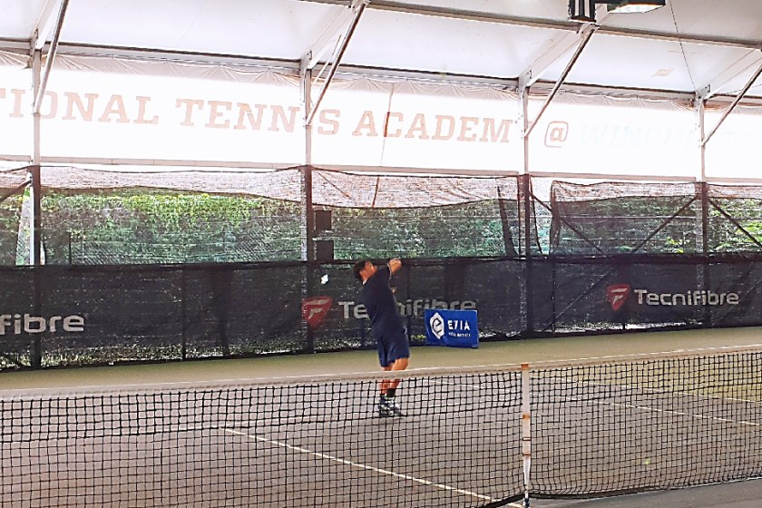 Coach Bo Alburo's shoulder is greatly turned to hit the backhand overhead smash