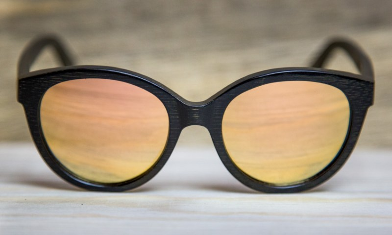 Lola 2.0s sit on a wooden bade. They are a curved frame sunglasses.
