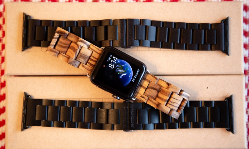 Three wooden apple watch bands are laid across a display. Two are made from Ebony wood and the other is made from Zebrawood.