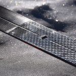 "The fish scale pattern of a Fischer S-Bound classic waxless backcrountry cross-country ski. This pattern is more aggressive than typical waxless fish scale patterns. The hole in the center of the ski is an attachment point for ""skins,"" which provide extra grip (particularly over icy snow). Also note that the lighting has been maximized to show texture rather than color. © Jared Manninen"