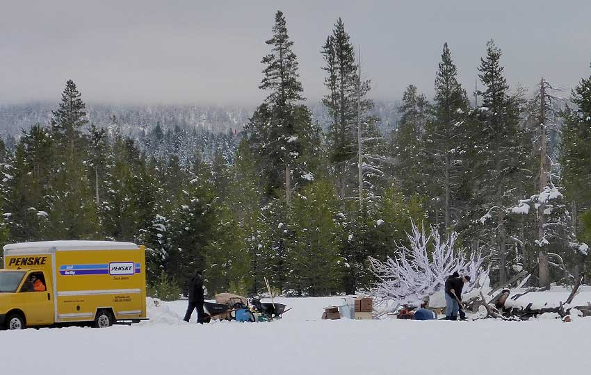 Crew members prepare a filming location in the snowy meadow for a winter scene in Top Gun: Maverick