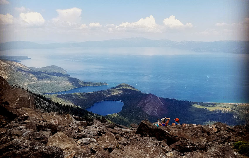 Hikers enjoying views of multiple small lakes in addition to Lake Tahoe on a partially cloudy day