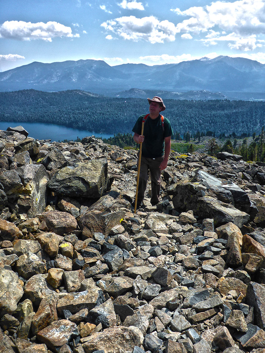 Hiker with brimmed hat and walking stick standing on talus with mountains in the distance